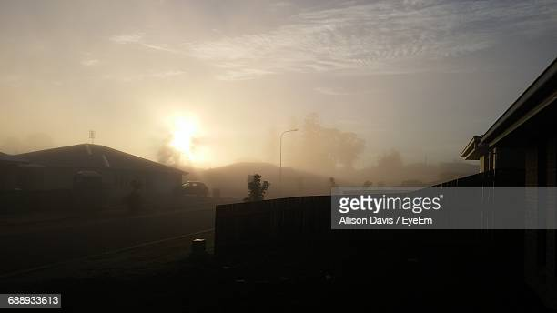 Silhouette Houses And Road Against Sky During Sunrise In Foggy Weather