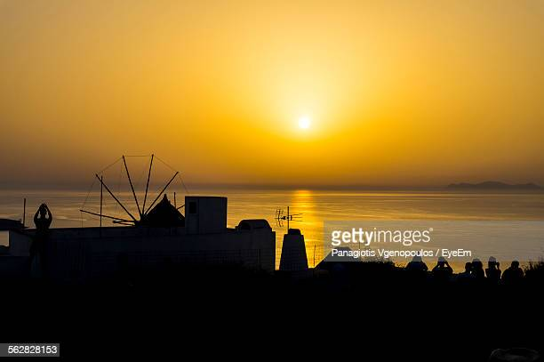 silhouette houses in front of sea against sky during sunset - vgenopoulos stock pictures, royalty-free photos & images