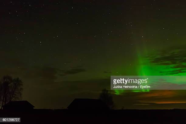 silhouette houses on field against aurora in sky - heinovirta stock photos and pictures