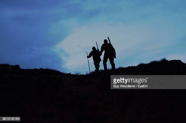 silhouette hunters hiking on field against sky - hunting stock pictures, royalty-free photos & images