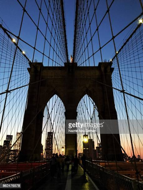 A silhouette image on a famous Brooklyn bridge at dusk.