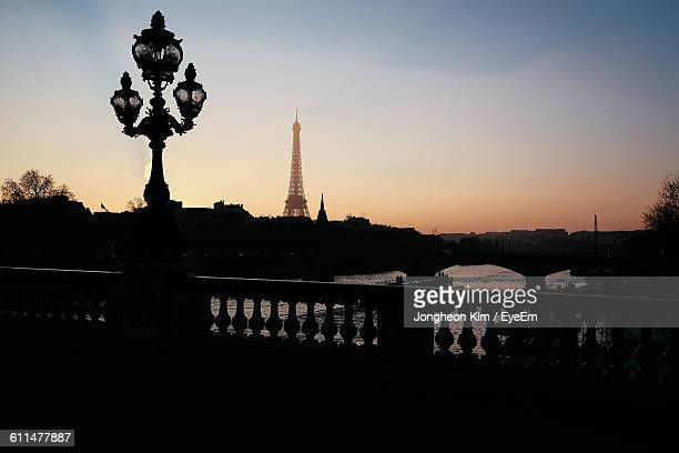 Silhouette Lamp Post On Bridge With Eiffel Tower In Background Against Sky During Sunset