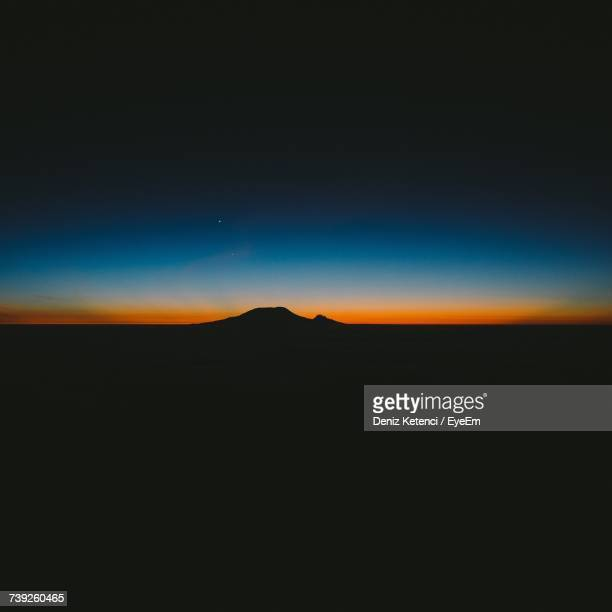 Silhouette Landscape Against Clear Sky At Night