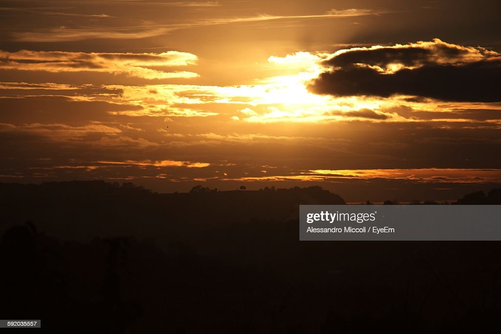 Silhouette Landscape Against Cloudy Sky At Sunset : Stock Photo