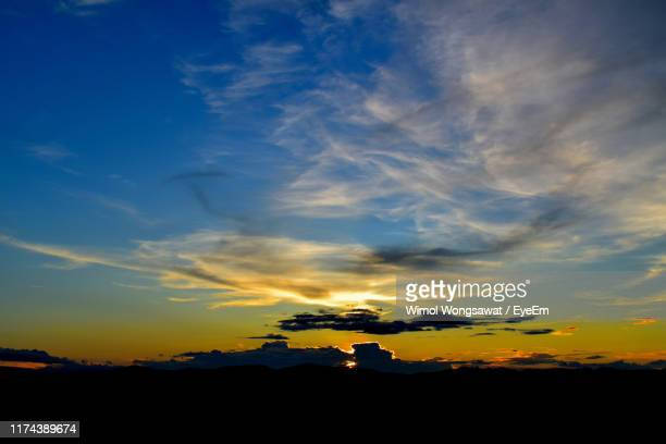 silhouette landscape against dramatic sky during sunset - wimol wongsawat stock photos and pictures