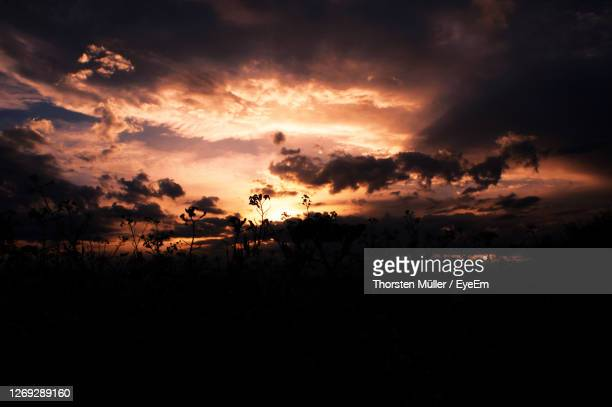 silhouette landscape against dramatic sky during sunset - dämmerung stock pictures, royalty-free photos & images