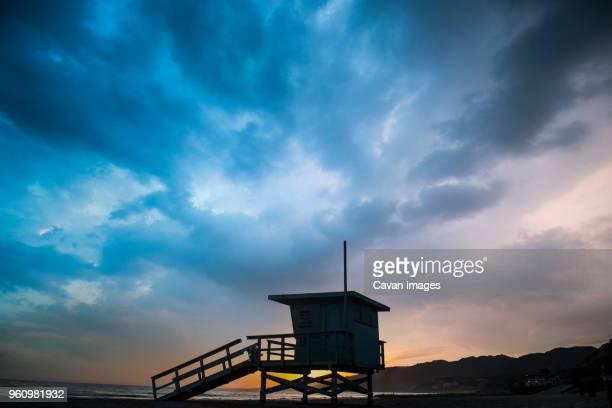 Silhouette lifeguard hut on sand against cloudy sky at Venice beach