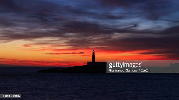 silhouette lighthouse by sea against orange sky - prison building stock pictures, royalty-free photos & images