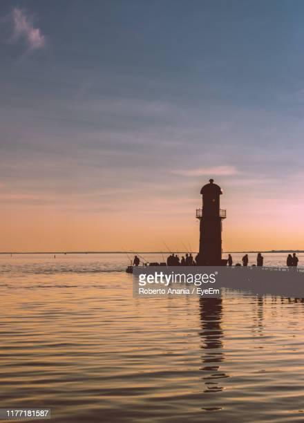 silhouette lighthouse by sea against sky during sunset - quebec stock pictures, royalty-free photos & images