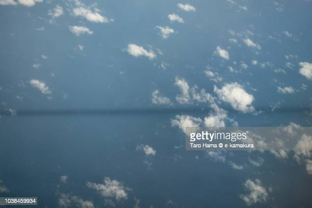 Silhouette line of vapor trail reflecting on Pacific Ocean daytime aerial view from airplane