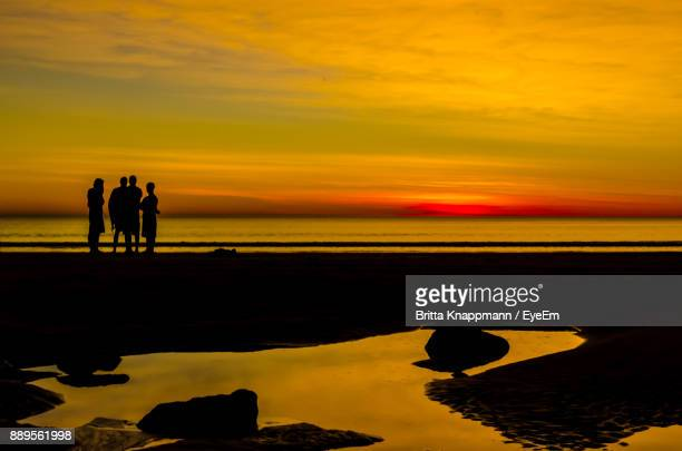 Silhouette Male Friends Standing At Beach Against Orange Sky