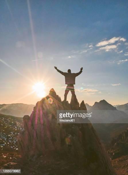 silhouette male hiker standing with arms outstretched on mountain during sunset, leon, spain - comunidad autónoma de castilla y león fotografías e imágenes de stock