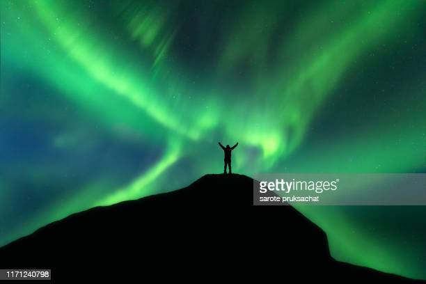 silhouette male hikers on mountain peak and northern light backgrounds . success and leadership concept . - noord stockfoto's en -beelden