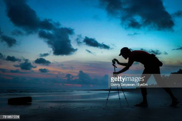 silhouette man adjusting mobile phone on tripod at shore against cloudy sky - tripod stock pictures, royalty-free photos & images