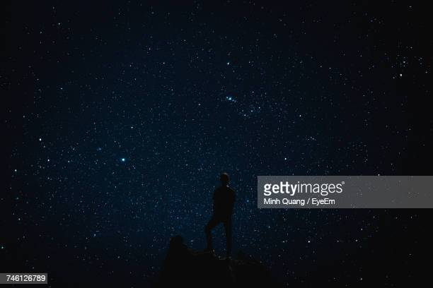 silhouette man against sky at night - costellazione foto e immagini stock