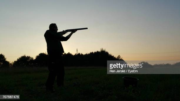 Silhouette Man Aiming With Shotgun On Field Against Clear Sky During Sunset