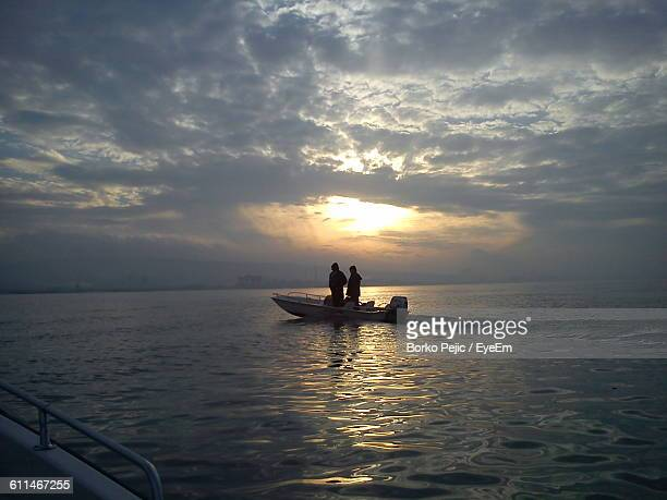 Silhouette Man And Woman Sailing On Motorboat In Sea At Sunset