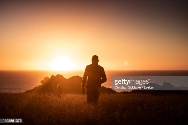 silhouette man and woman standing against sea and sky during sunset - christian soldatke stock pictures, royalty-free photos & images