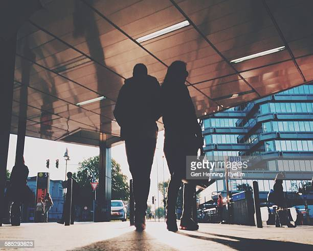 silhouette man and woman walking towards street - duisburg imagens e fotografias de stock