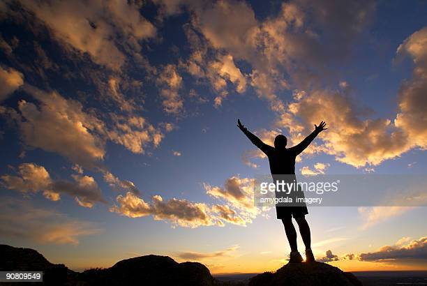 silhouette man arms raised sunset sky landscape - sandia mountains stock photos and pictures
