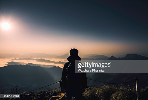 silhouette man at peak of mountains
