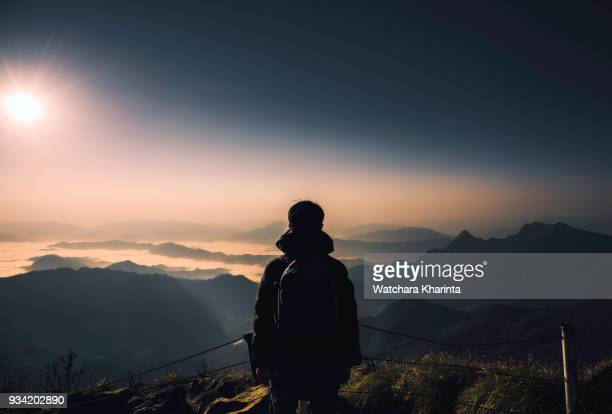 silhouette man at peak of mountains - zonsopgang stockfoto's en -beelden