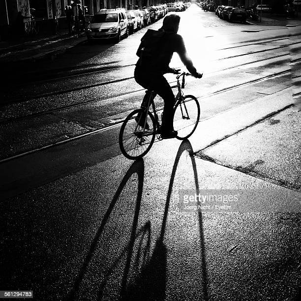 Silhouette Man Bicycling On Road