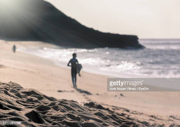silhouette man carrying surfboard at beach - torquay,_victoria stock pictures, royalty-free photos & images