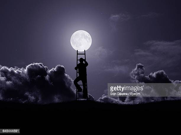 silhouette man climbing ladder and reaching towards moon at night - ladder to the moon stock pictures, royalty-free photos & images