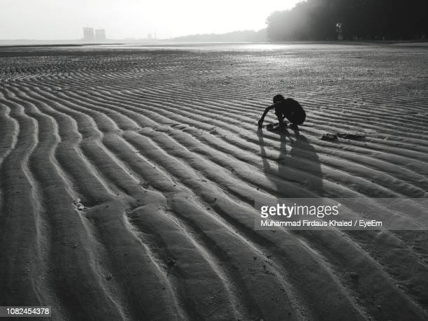 silhouette man crouching on beach against sky - only mid adult men stock pictures, royalty-free photos & images