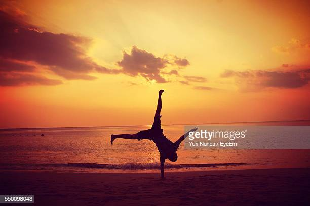 Silhouette Man Doing Handstand On Beach At Sunset