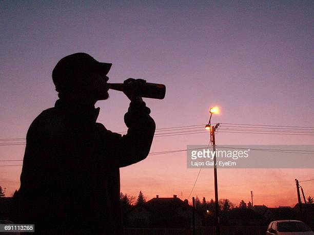 Silhouette Man Drinking Beer Against Clear Sky At Dusk