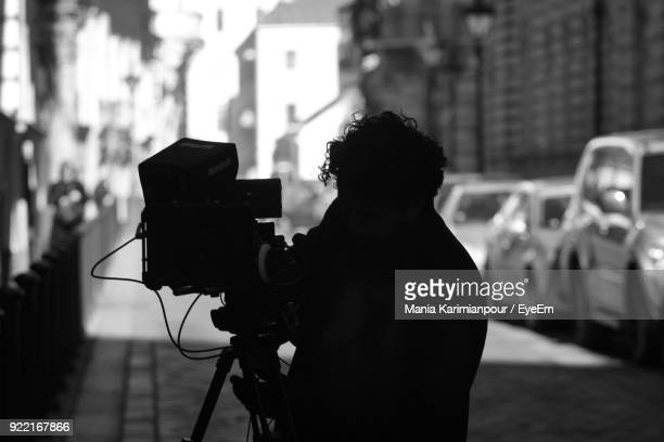 silhouette man filming with television camera on street - film crew stock pictures, royalty-free photos & images