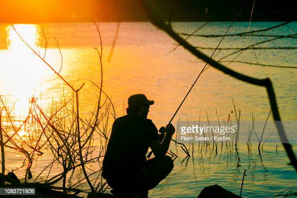 silhouette man fishing by lake against sky during sunset - florin seitan stock pictures, royalty-free photos & images