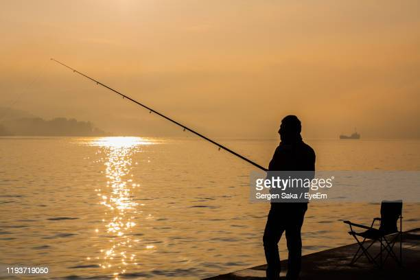 silhouette man fishing by sea against sky during sunset - saka stock pictures, royalty-free photos & images