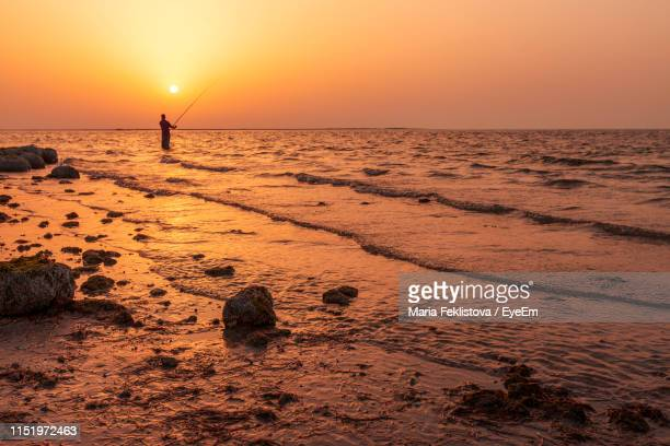 silhouette man fishing in sea against clear sky during sunset - pays du golfe photos et images de collection