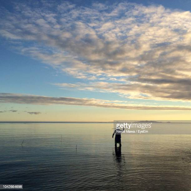 silhouette man fishing in sea against cloudy sky - spear stock photos and pictures