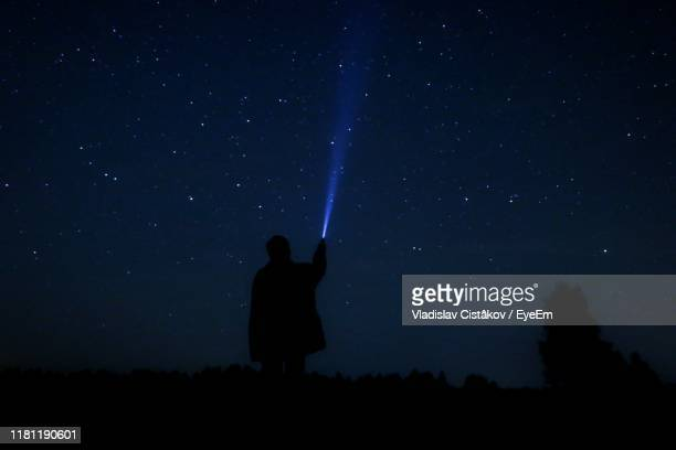 silhouette man flashing light on field against sky at night - space exploration stock pictures, royalty-free photos & images
