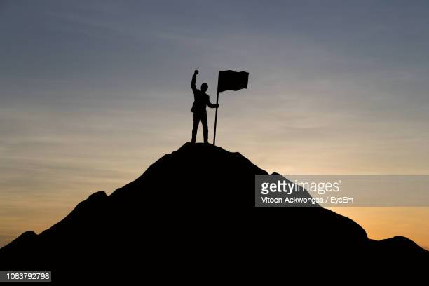 silhouette man holding flag while standing on mountain against sky during sunset - 旗 ストックフォトと画像