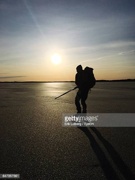 Silhouette Man Holding Ice Rod On Frozen Lake Against Sky
