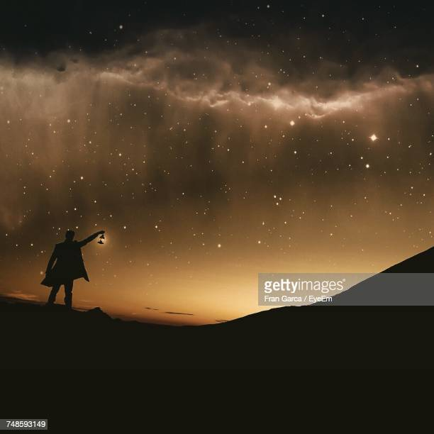 silhouette man holding lantern against starry sky at night - lantern stock pictures, royalty-free photos & images