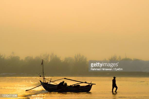 silhouette man in boat against sky during sunset - rahmad himawan stock pictures, royalty-free photos & images