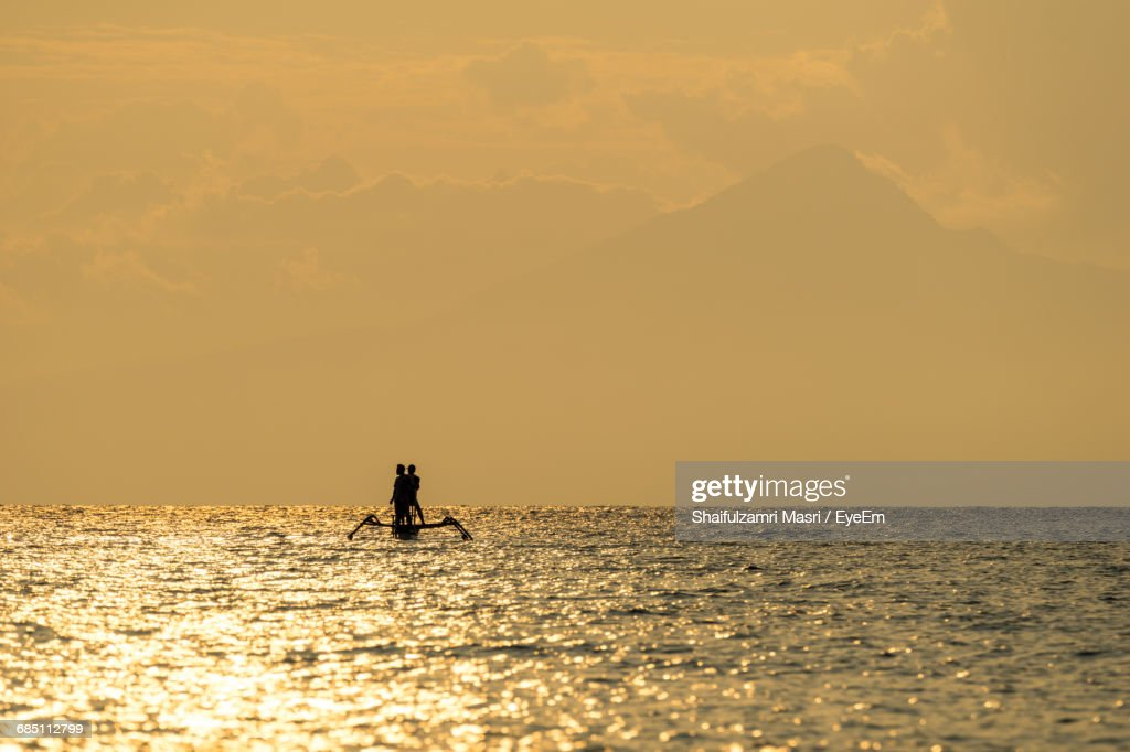 Silhouette Man In Sea Against Sky During Sunset : Stock Photo