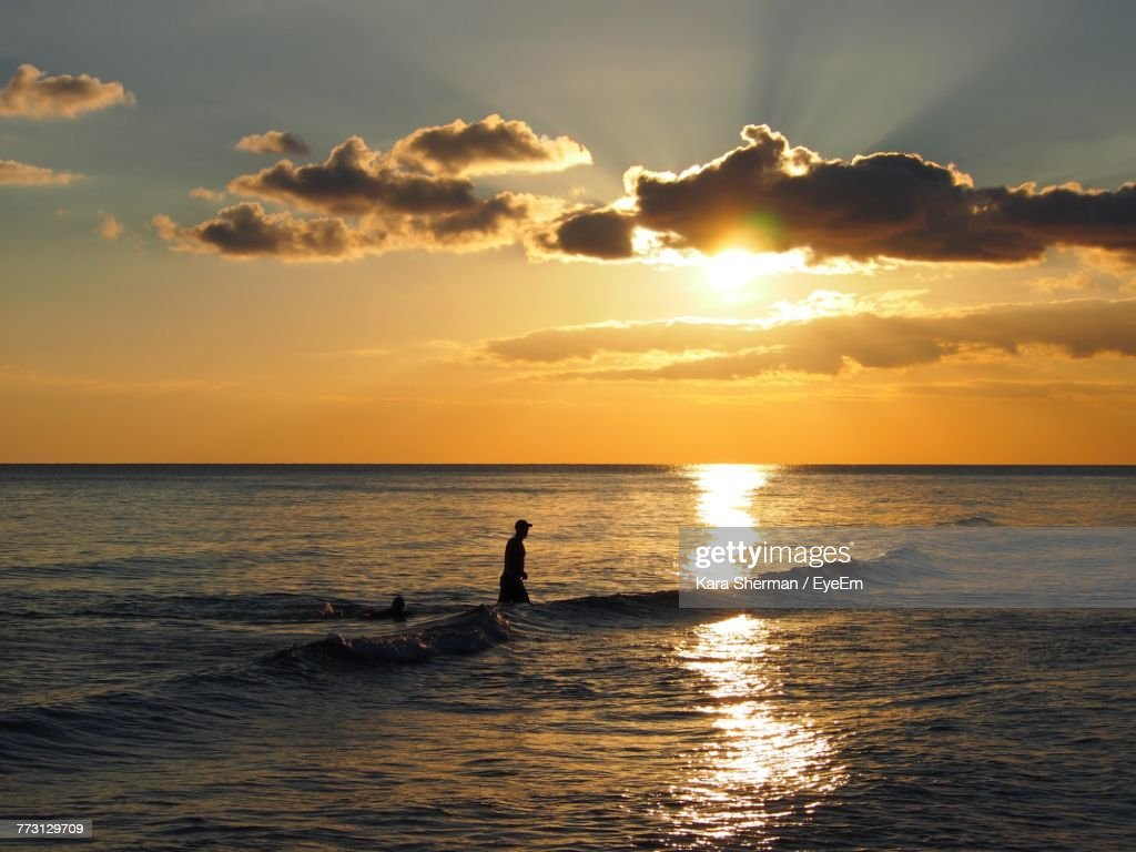Silhouette Man In Sea Against Sky During Sunset : Photo