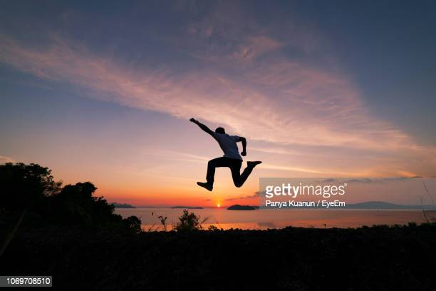 silhouette man jumping against sky during sunset - gesturing stock pictures, royalty-free photos & images