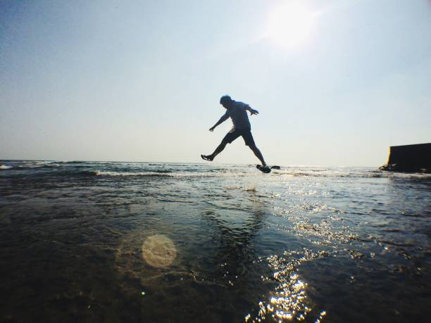 Silhouette Man Jumping At Beach Against Clear Sky
