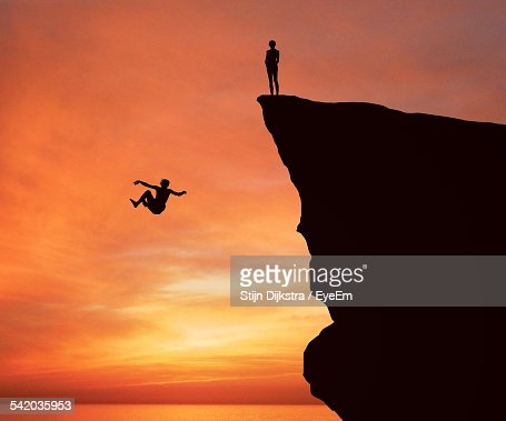 Silhouette Man Jumping From Cliff Into Lake Against Orange Sky