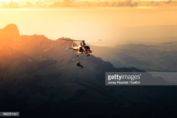 silhouette man jumping from helicopter - euforie stockfoto's en -beelden