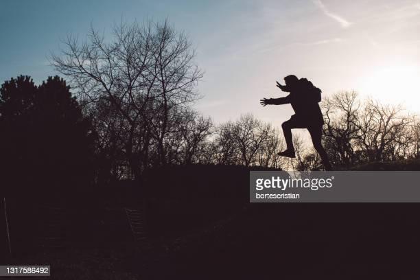 silhouette man jumping on bare tree against sky - bortes stockfoto's en -beelden