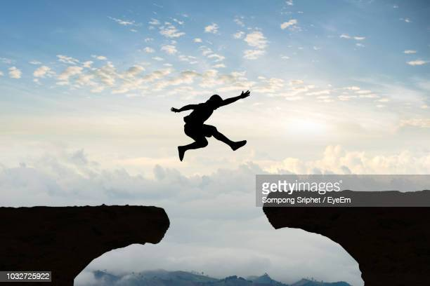 silhouette man jumping over cliffs against cloudy sky - 崖 ストックフォトと画像